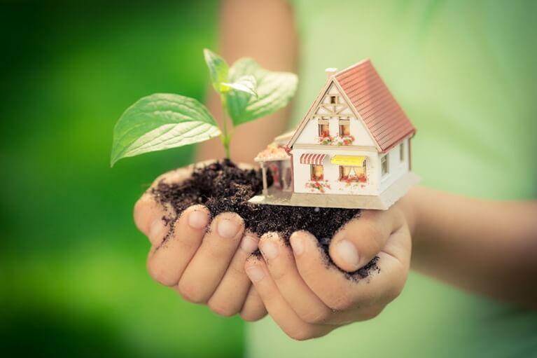 Παιδικά χέρια που κρατάνε ένα μικρό σπιτάκι με χώμα για να δείξουν την ενεργειακή αναβάθμιση που γίνεται στο εξοικονομω κατ οικον